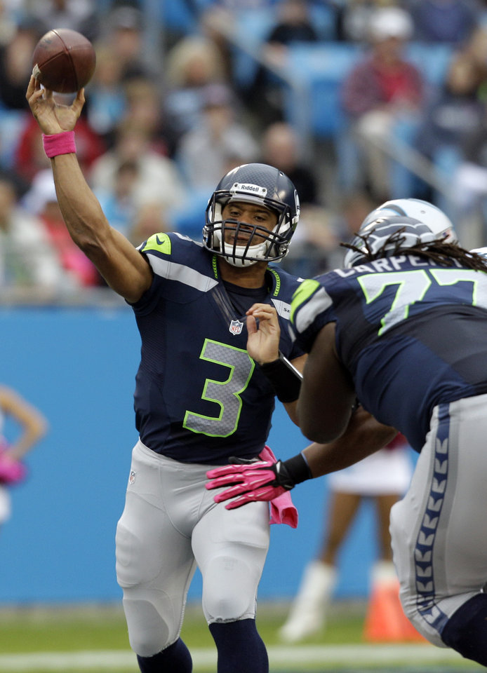 Photo -   Seattle Seahawks' Russell Wilson (3) throws a pass under pressure during the first quarter of an NFL football game against the Carolina Panthers in Charlotte, N.C., Sunday, Oct. 7, 2012. (AP Photo/Chuck Burton)
