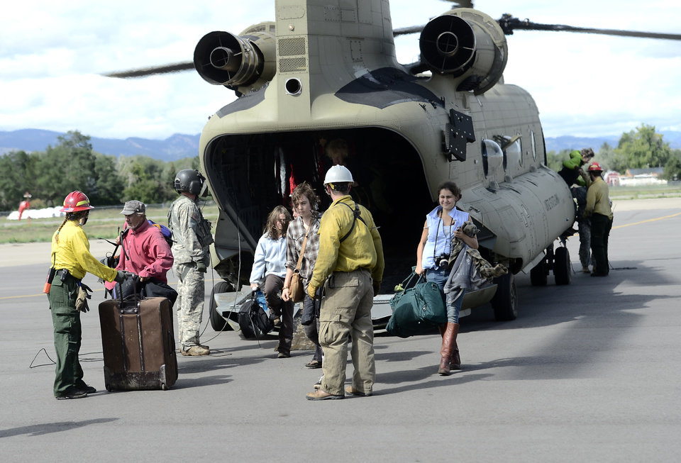 Photo - People are directed off the tarmac at Boulder Municipal Airport after being flown down from Jamestown on a National Guard helicopter after being stranded from heavy rains in Boulder, Colorado Friday Sept. 13, 2013.(AP Photo/Daily Camera, Mark Leffingwell)