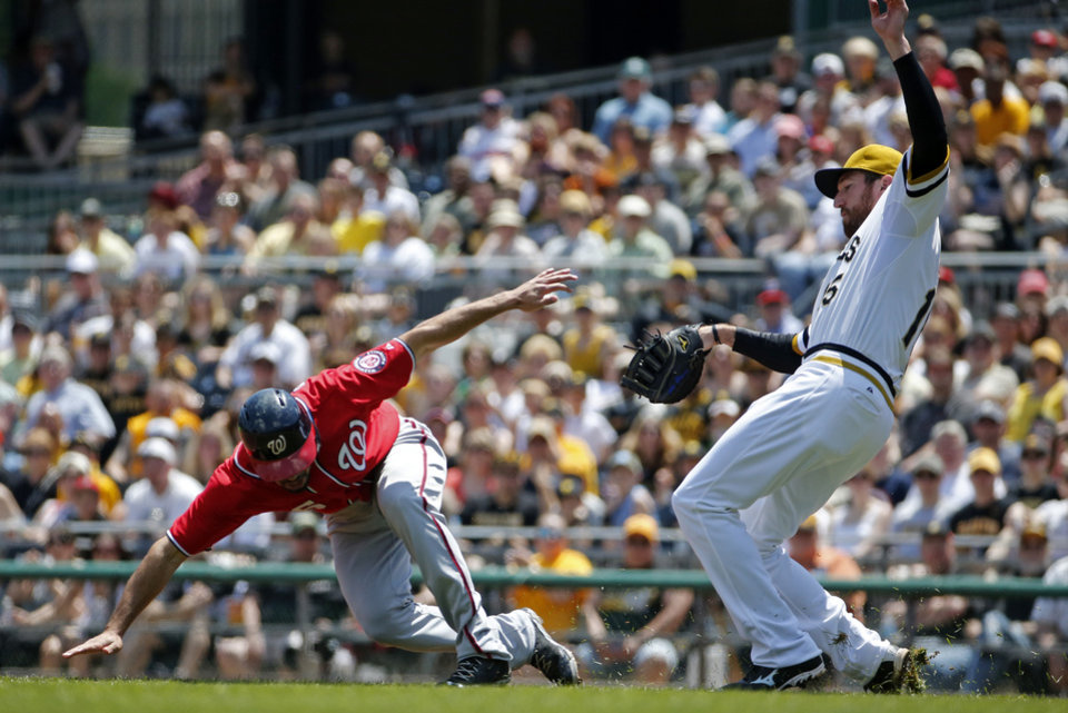 Photo - Pittsburgh Pirates first baseman Ike Davis, right, and Washington Nationals' Anthony Rendon, left, collide during a rundown between first and second during the third inning of a baseball game in Pittsburgh Sunday, May 25, 2014. Rendon was awarded second base on the error by Davis. (AP Photo/Gene J. Puskar)