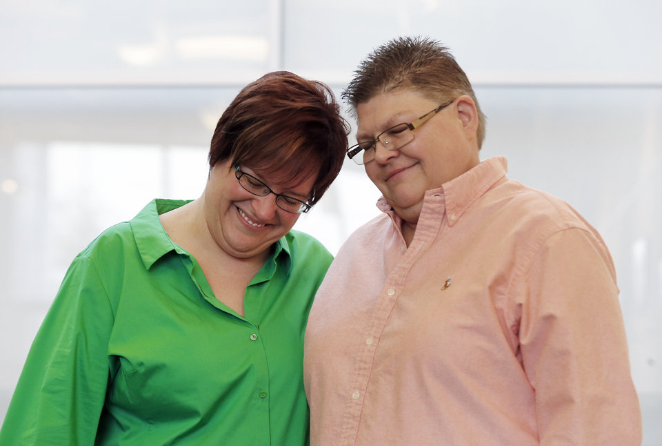 Photo - April DeBoer, left, and Jayne Rowse, react during a news conference in Ferndale, Mich., Friday, March 21, 2014. A federal judge has struck down Michigan's ban on gay marriage Friday the latest in a series of decisions overturning similar laws across the U.S. The two nurses who've been partners for eight years claimed the ban violated their rights under the U.S. Constitution. (AP Photo/Paul Sancya)