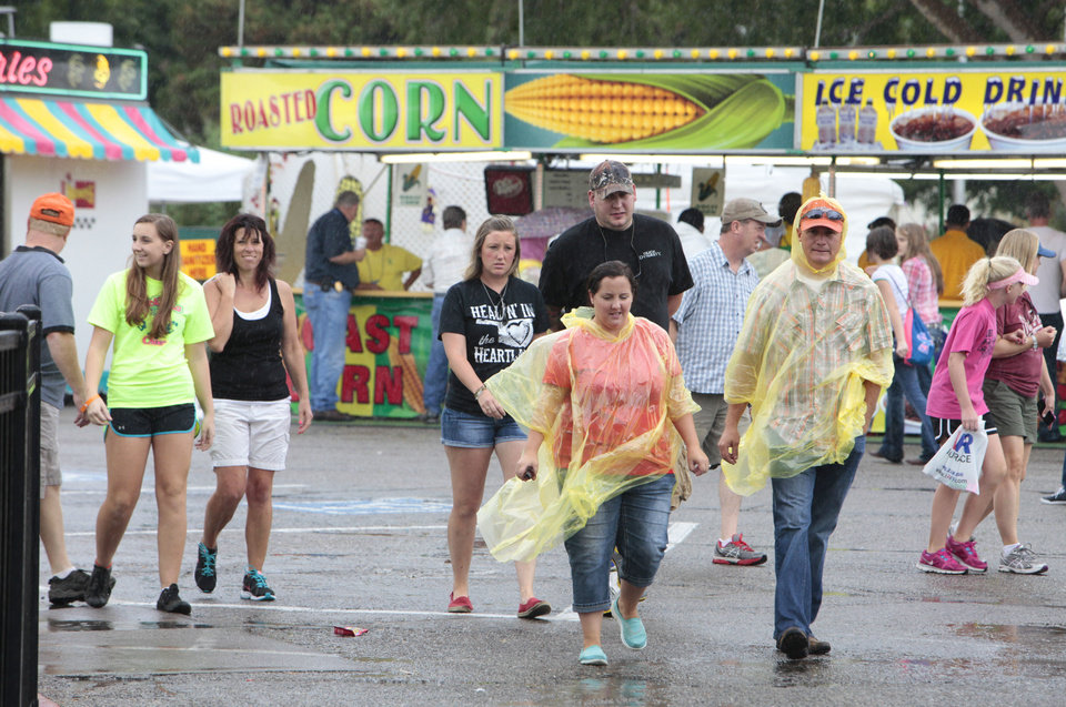 Photo - Rain soaked patrons at the Oklahoma State Fair , Friday, September 13, 2013.  Photo by David McDaniel, The Oklahoman