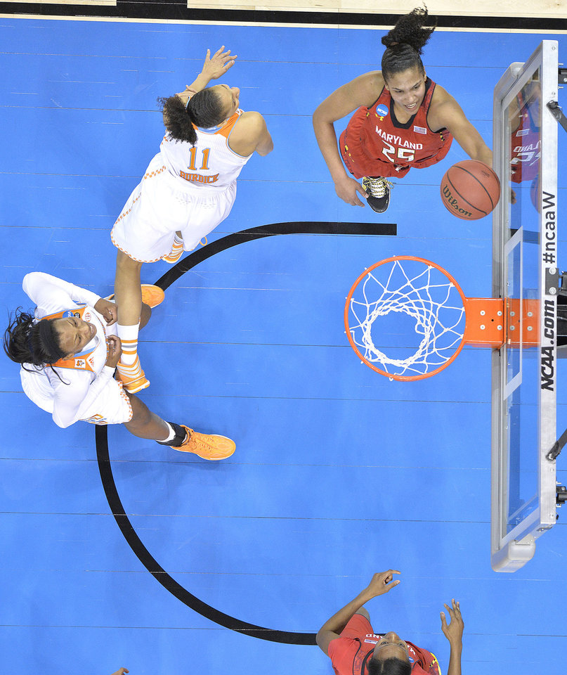 Photo - Maryland's Alyssa Thomas, top right, shoots past the defense of Tennessee's Cierra Burdick during the second half in a regional semifinal game at the NCAA women's college basketball tournament on Sunday, March 30, 2014, in Louisville, Ky. Maryland defeated Tennessee 73-62. (AP Photo/Timothy D. Easley)