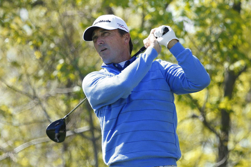 Photo - Lee Rinker watches his tee shot on the 10th hole during the first round of the 75th Senior PGA Championship golf tournament at the Harbor Shores Golf Club in Benton Harbor, Mich., Thursday, May 22, 2014.  (AP Photo/Paul Sancya)