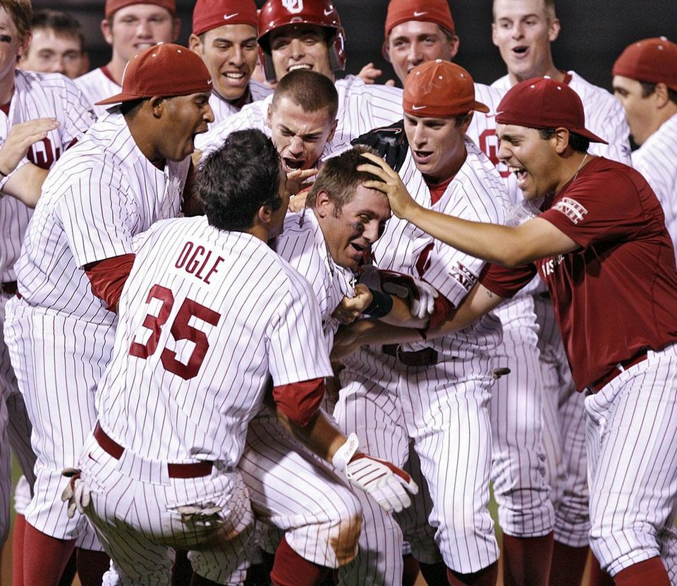 Photo -  Sooners mob teammate Cody Reine, right, after his hit to drive in two runs in the bottom of the ninth inning to give the Sooners a 3-2 win over Kansas in the fourth game of the Big 12 Baseball Championship between Oklahoma and Kansas at the Bricktown Ballpark on Wednesday, May 26, 2010, in Oklahoma City, Okla.  Photo by Chris Landsberger, The Oklahoman