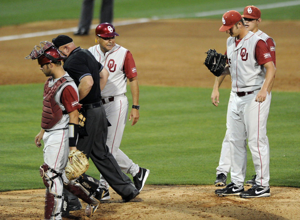 Photo - Oklahoma's coach Sunny Golloway, third from left, is escorted off the field after talking to his pitcher Jordan John, second from right, on the mound against South Carolina in the third  inning of an NCAA college super regional baseball tournament game in Columbia, S.C., Saturday, June 9, 2012. (AP Photo/Mary Ann Chastain) ORG XMIT: SCMC103