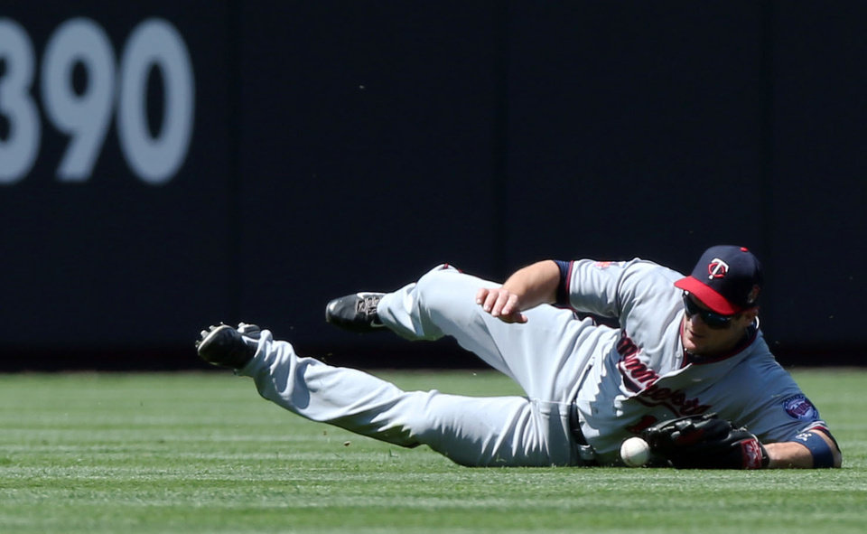 Photo - Minnesota Twins left fielder Josh Willingham dives but misses a ball that went for a double  by Colorado Rockies' Nolan Arenado in the first inning of an interleague baseball game in Denver on Sunday, July 13, 2014. (AP Photo/David Zalubowski)