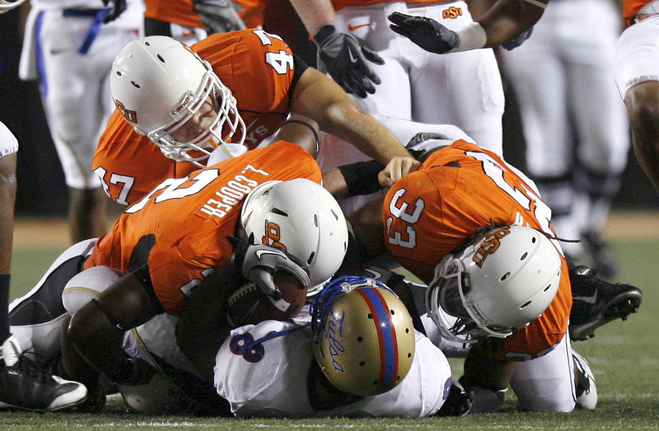 Photo - Oklahoma State safety Lavocheya Cooper (2), Oklahoma State defensive end Will Garrett (47) and Oklahoma State linebacker LeRon Furr (33) tackle Tulsa running back Alex Singleton (8) during the college football game between the University of Tulsa (TU) and Oklahoma State University (OSU) at Boone Pickens Stadium in Stillwater, Oklahoma, Saturday, September 18, 2010. Photo by Sarah Phipps, The Oklahoman