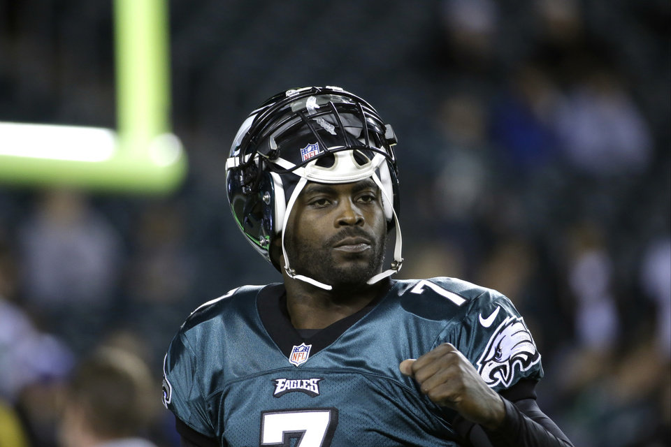 Photo - FILE - In a Dec. 22, 2013 file photo, Philadelphia Eagles' Michael Vick warms up before the first half of an NFL football game between the Philadelphia Eagles and the Chicago Bears, in Philadelphia. The New York Jets signed quarterback Michael Vick and released Mark Sanchez on Friday, March 21, 2014. Vick was a free agent after spending the last five seasons with the Phialdelphia Eagles. (AP Photo/Matt Rourke, File)