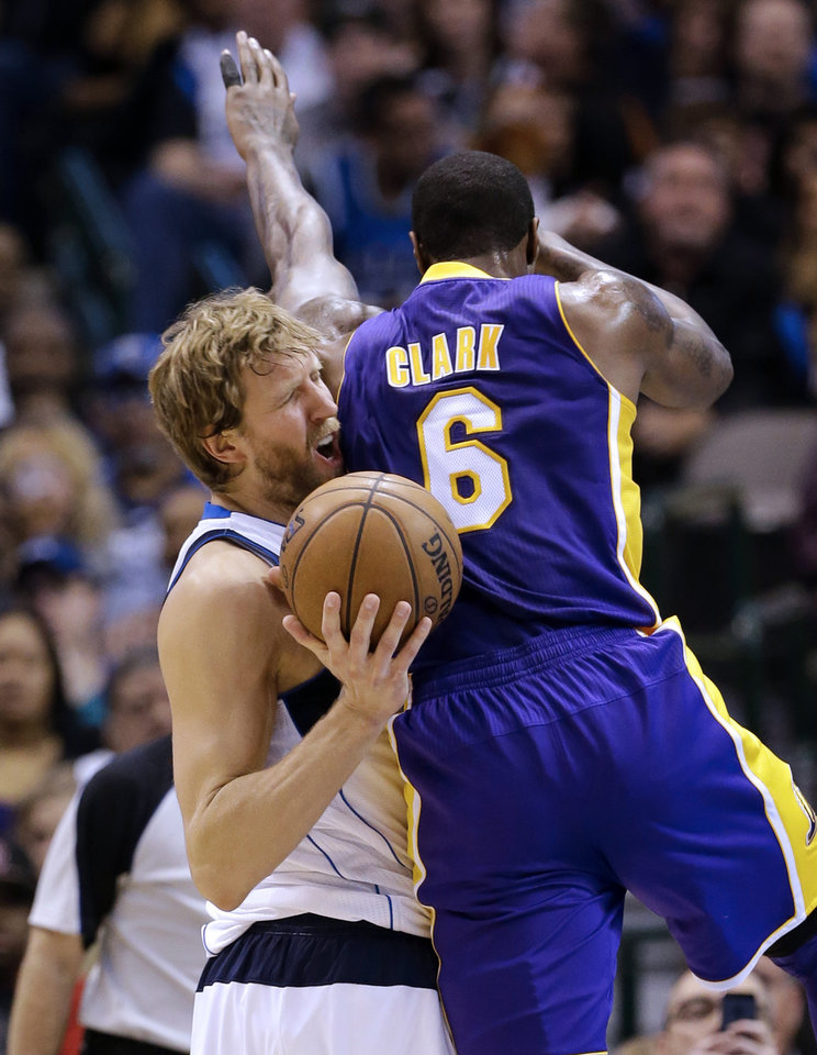 Dallas Mavericks' Dirk Nowitzki (41) of Germany is fouled on a shot attempt by Los Angeles Lakers' Earl Clark (6) in the first  half of an NBA basketball game Sunday, Feb. 24, 2013, in Dallas. (AP Photo/Tony Gutierrez)