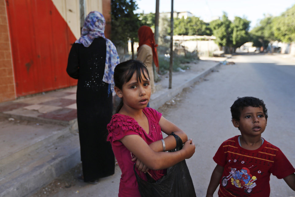Photo - Palestinians flee their homes in the Shajaiyeh neighborhood of Gaza City, after Israel had airdropped leaflets warning people to leave the area, Wednesday, July 16, 2014. Palestinians flee their home in Gaza City, Wednesday, July 16, 2014. Alongside the air strikes, Israel also ordered tens of thousands of residents of the northern town of Beit Lahiya and the Zeitoun and Shijaiyah neighborhoods of Gaza City, all near the border with Israel, to evacuate their homes by 8 a.m. Wednesday. The warnings were delivered in automated phone calls, text messages and leaflets.(AP Photo/Lefteris Pitarakis)