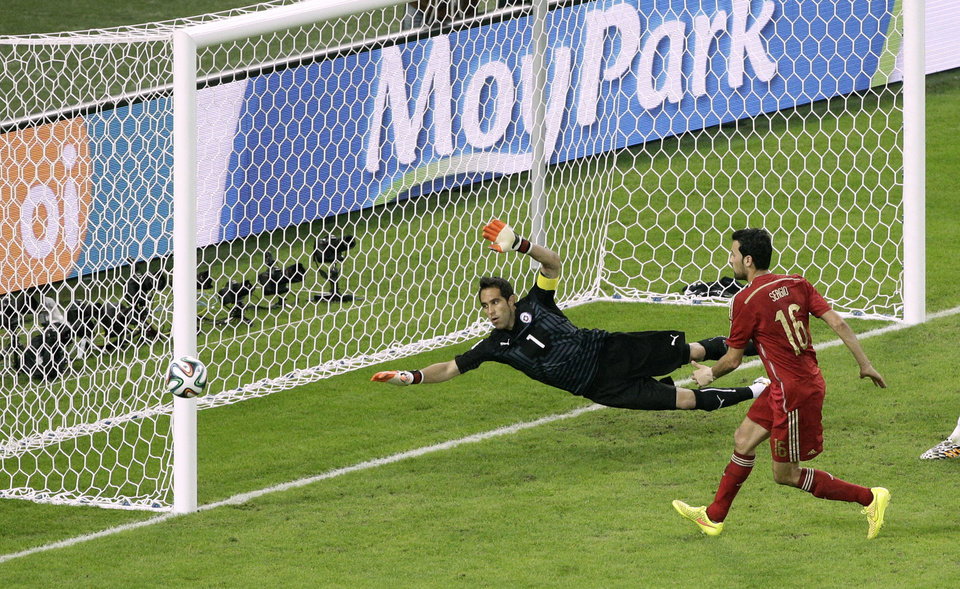 Photo - Spain's Sergio Busquets, right, shoots past the goal of Chile's goalkeeper Claudio Bravo during the group B World Cup soccer match between Spain and Chile at the Maracana Stadium in Rio de Janeiro, Brazil, Wednesday, June 18, 2014.  (AP Photo/Christophe Ena)