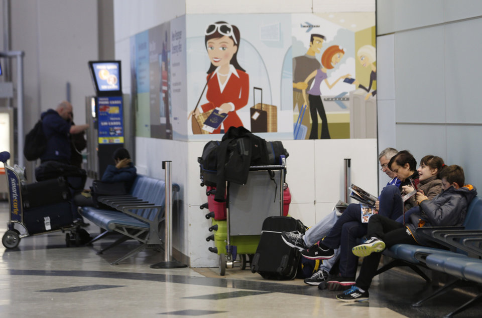 Photo - People sit near their luggage at Newark Liberty International Airport, Thursday, Dec. 27, 2012 in Newark, N.J. An overnight storm caused some delays at the airport. (AP Photo/Julio Cortez)