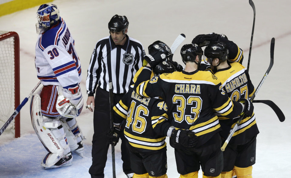 Photo - Boston Bruins defenseman Zdeno Chara (33) is congratulated by teammates after scoring against New York Rangers goalie Henrik Lundqvist (30) during the second period in Game 1 of an NHL hockey playoffs Eastern Conference semifinal game in Boston, Thursday, May 16, 2013. (AP Photo/Charles Krupa)