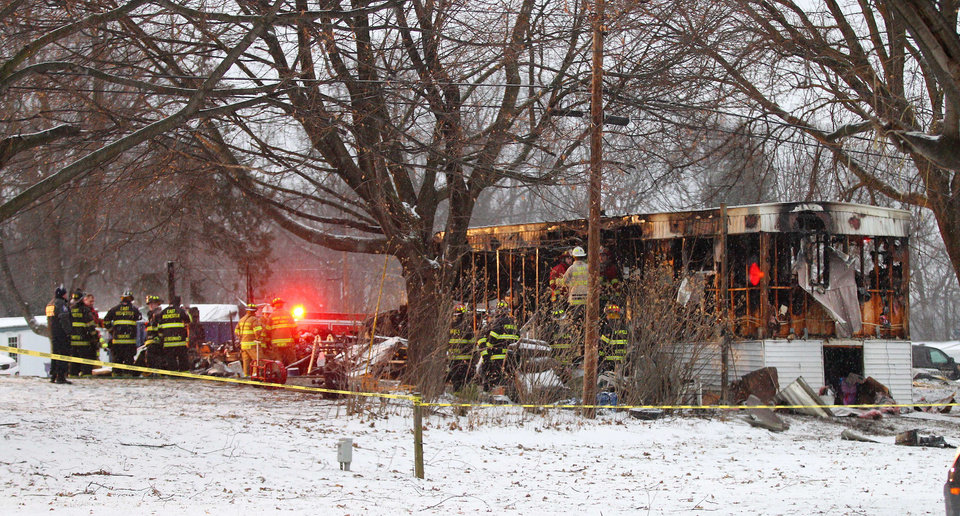 Photo - In this Jan. 20, 2014 photo, firefighters investigate a fatal fire in a mobile home in Penfield, N.Y. Eight-year-old Tyler Doohan died in the flames while trying to save his handicapped grandfather. Doohan's grandfather and uncle died along with him but fire fighters are calling him a hero. Six people got out of the burning trailer alive because he woke them up. (AP Photo/Rochester Democrat and Chronicle, Jamie Germano) MAGS OUT. NO SALES.