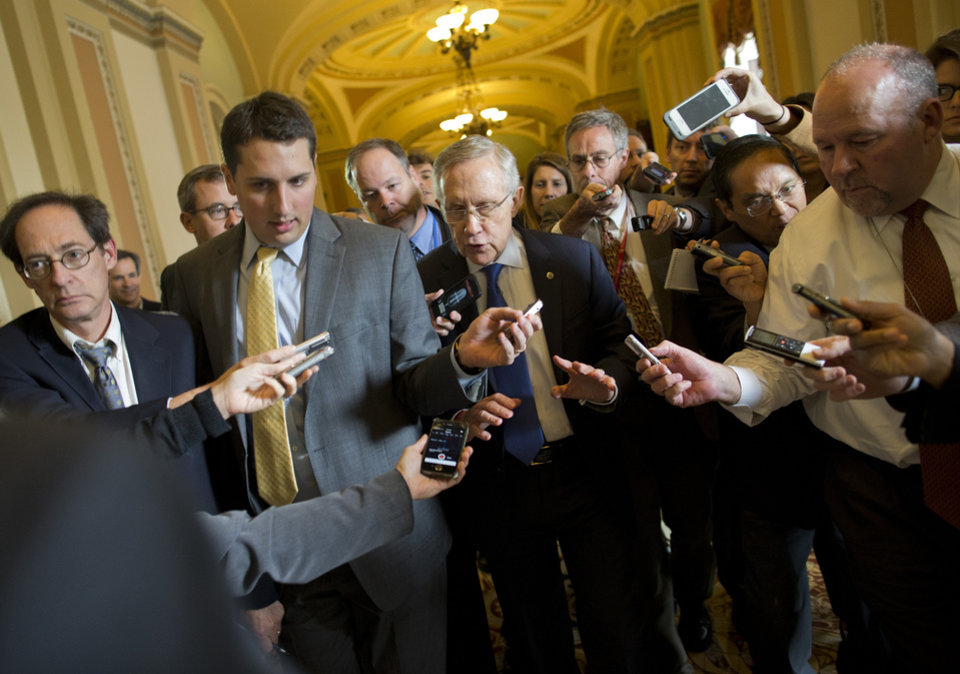 Photo - Senate Majority Leader Sen. Harry Reid, D-Nev., is surrounded by reporters after leaving the office of Senate Minority Leader Sen. Mitch McConnell, R-Ken., on Capitol Hill on Monday, Oct. 14, 2013 in Washington. Reid reported progress Monday toward a deal to avoid a threatened default and end a two-week partial government shutdown as President Barack Obama called congressional leaders to the White House to press for an end to the impasse.