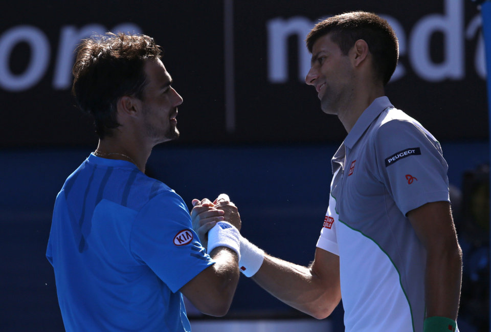 Photo - Novak Djokovic of Serbia, right, shakes hands with Fabio Fognini of Italy after Djokovic won their fourth round match at the Australian Open tennis championship in Melbourne, Australia, Sunday, Jan. 19, 2014.(AP Photo/Eugene Hoshiko)