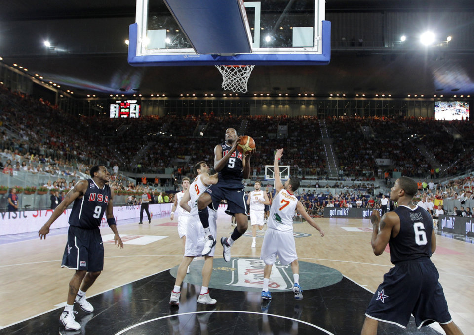 United States Kevin Durant, center, drives with the ball past Spain's Felipe Reyes, center left, and Juan Carlos Navarro, center right, during a friendly basketball game in Madrid on Sunday, Aug. 22, 2010. (AP Photo/Daniel Ochoa de Olza) ORG XMIT: DO127