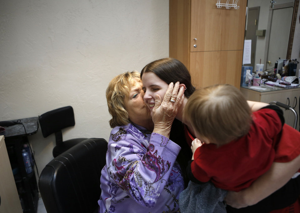 Photo - Vona Hankins kisses Deanna Tucker after cutting the hair of Nathan Marshall, who is the sixth generation of a family that has been seeing Hankins for haircuts in Oklahoma City, Friday, Nov. 16, 2012.  Photo by Garett Fisbeck, The Oklahoman