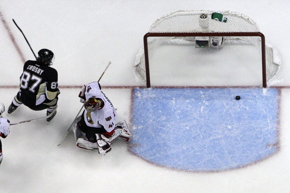 Photo - Pittsburgh Penguins' Sidney Crosby (87) scores his second goal of the first period on Ottawa Senators goalie Craig Anderson (41) in Game 2 of an NHL hockey Stanley Cup second-round playoff series, in Pittsburgh on Friday, May 17, 2013. The Penguins won 4-3. (AP Photo/Gene J. Puskar)