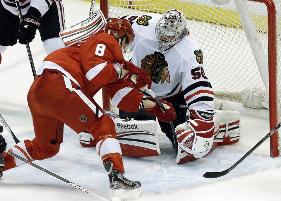 Photo - Chicago Blackhawks goalie Corey Crawford (50) stops a shot by Detroit Red Wings left wing Justin Abdelkader (8) during the second period in Game 4 of the Western Conference semifinals in the NHL hockey Stanley Cup playoffs in Detroit, Thursday, May 23, 2013. (AP Photo/Paul Sancya)