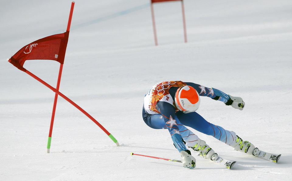 Photo - United States' Bode Miller passes a gate in the first run of the men's giant slalom at the Sochi 2014 Winter Olympics, Wednesday, Feb. 19, 2014, in Krasnaya Polyana, Russia. (AP Photo/Christophe Ena)