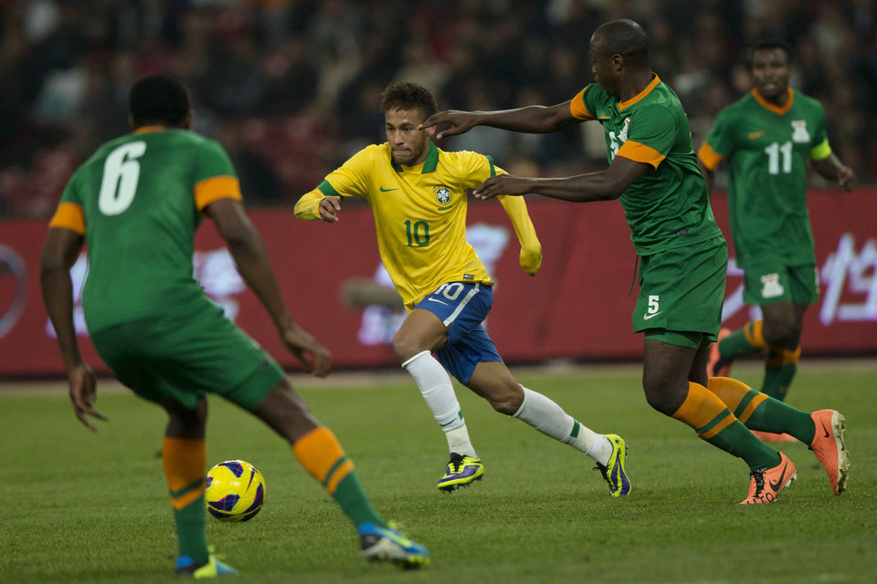 Photo - Brazil's Neymar, center tries to get the ball past Zambia's Chamba Bronson (6), Himonde Hichani (5) and Katongo Christopher (11) during a friendly match held at the Bird's Nest national stadium in Beijing, China, Tuesday, Oct. 15, 2013. Brazil won 2-0. (AP Photo/Ng Han Guan)
