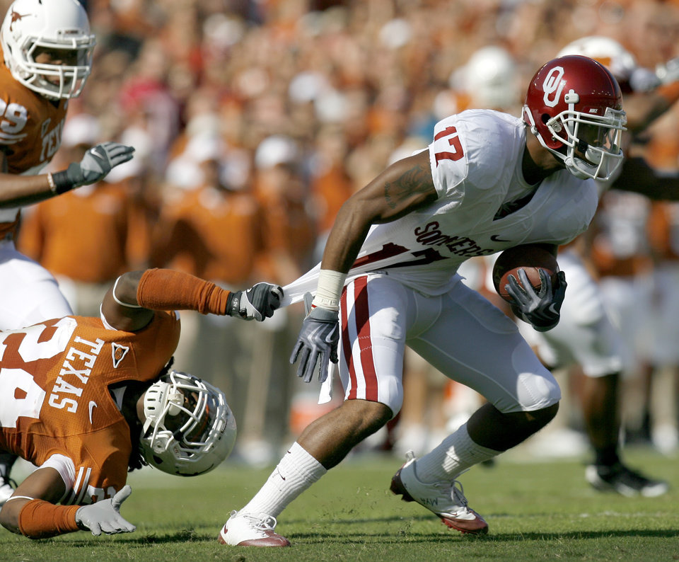 Photo - OU's Mossis Madu tries to get away from Antwan Cobb during the Red River Rivalry college football game between the University of Oklahoma Sooners (OU) and the University of Texas Longhorns (UT) at the Cotton Bowl in Dallas, Texas, Saturday, Oct. 17, 2009. Photo by Bryan Terry, The Oklahoman