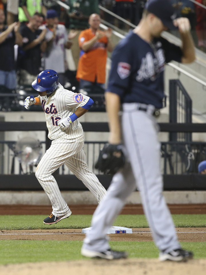 Photo - CORRECTS TO TWO-RUN HOME RUN  - New York Mets' Juan Lagares (12) rounds third base after hitting a two-run home run off of Atlanta Braves starting pitcher Alex Wood in the fourth inning of a baseball game Tuesday, Aug. 26, 2014, in New York. (AP Photo/John Minchillo)