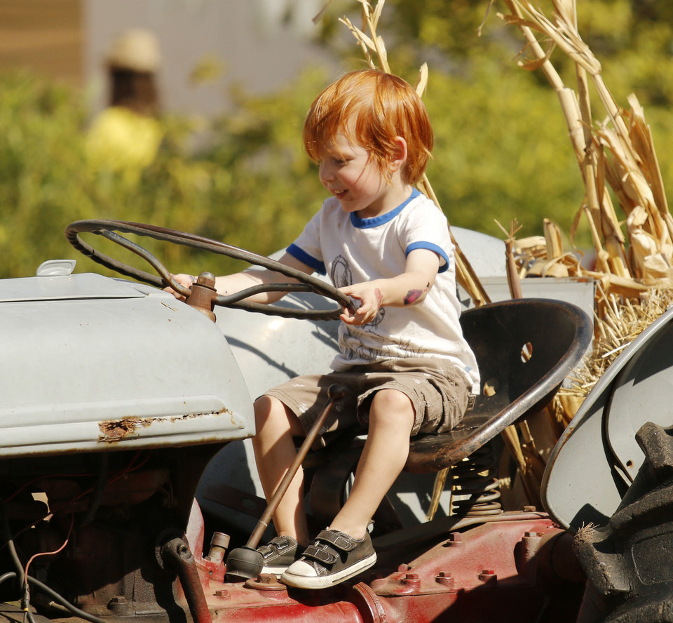 Photo -  Benjamin Neville-Lee, 2, sits on a tractor in Pumpkinville at the Mryiad Botanical Gardens during a preview party on Friday.  PHOTO BY DOUG HOKE, THE OKLAHOMAN  DOUG HOKE - THE OKLAHOMAN