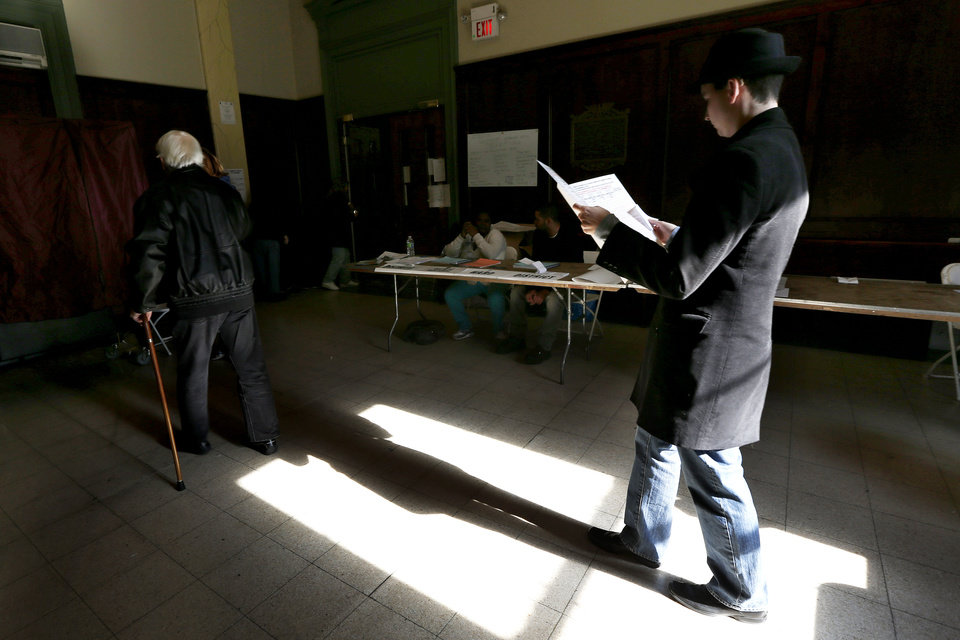 Photo - Sunlight shines on a man as he reads over a sample ballot while waiting in line to cast his vote at Hoboken City Hall on Election Day, Tuesday, Nov. 6, 2012, in Hoboken, N.J.  Voting in the U.S. presidential election was the latest challenge for the hundreds of thousands of people in the New York-New Jersey area still affected by Superstorm Sandy, as they struggled to get to non-damaged polling places to cast their ballots in one of the tightest elections in recent history. (AP Photo/Julio Cortez) ORG XMIT: NJJC126
