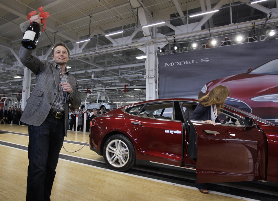Photo - FILE - In this June 22, 2012 file photo, Tesla Motors Inc. CEO Elon Musk holds up a bottle of wine given as a gift from one of their first customers, right, during a rally at the Tesla factory in Fremont, Calif. Tesla Motors says it is preparing a site near Reno, Nevada, as a possible location for its new battery factory, but is still evaluating other locations. (AP Photo/Paul Sakuma, File)