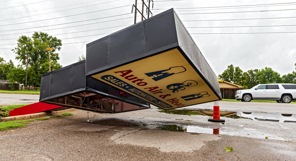 Photo - Strong storms knocked over the A&H Auto Air & Heat sign near Sunnylane and Fairview in Del City, Okla. on Tuesday, Aug. 27, 2019.   [Chris Landsberger/The Oklahoman]