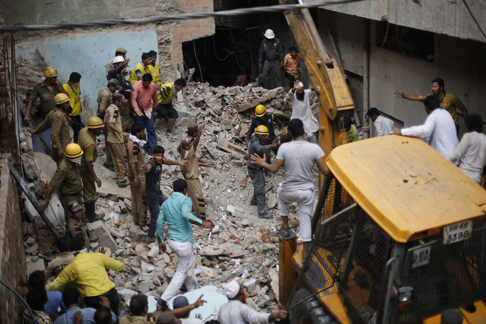 Photo - Indian rescuers gesture for an excavator to stop as they try to retrieve the body of a victim at the site of a building collapse in New Delhi, India, Saturday, June 28, 2014. A dilapidated building collapsed in the Indian capital on Saturday, killing at least seven people as rescuers searched for others believed to be trapped. (AP Photo/Altaf Qadri)