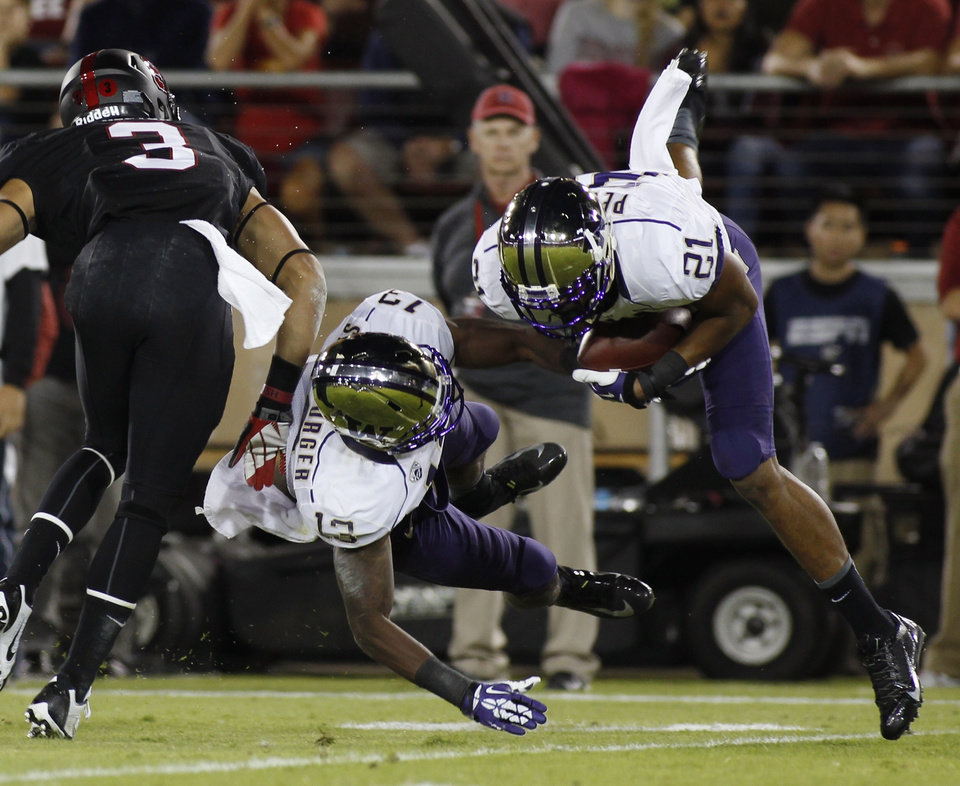 Photo - Washington's Marcus Peters, right, makes an interception against Stanford during the first half of an NCAA college football game in Stanford, Calif., Saturday, Oct. 5, 2013. At left are Stanford's Michael Rector and Washington's Will Shamburger. (AP Photo/George Nikitin)