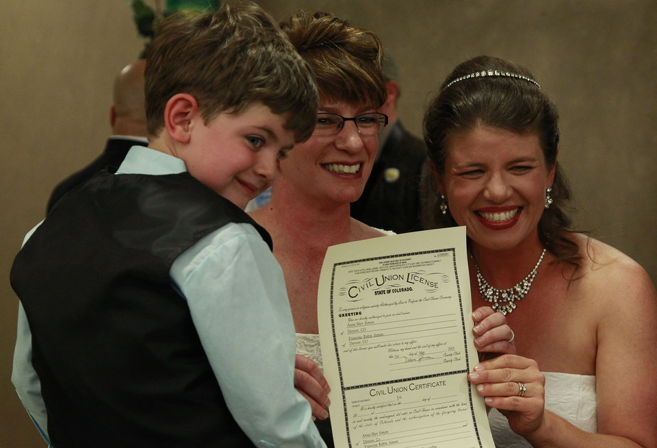 Photo - Just after midnight, Fran Simon, left, and her partner Anna Simon, flanked by their son Jeremy, age 5, display their State of Colorado civil union license shortly before making their vows during a ceremony at the Webb Municipal Building in Denver, Wednesday May 1, 2013. Fran Simon, left, and her partner Anna Simon were the first couple to receive a certificate. In March 2013, the Colorado General Assembly passed SB-11, the Colorado Civil Union Act, which provides committed same-sex couples with legal protections and responsibilities. The act went into effect on May 1, 2013. (AP Photo/Brennan Linsley)