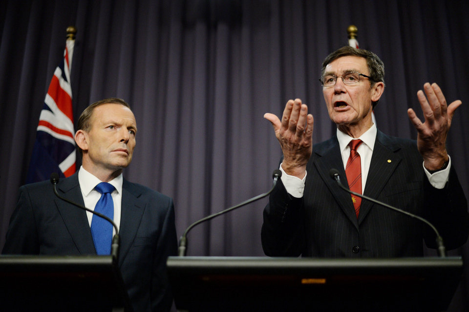 Photo - Prime Minister Tony Abbott, left, looks on as retired Chief Air Marshall Angus Houston, the head of the Joint Agency Coordination Centre, speaks to the media during a press conference at Parliament House in Canberra, Monday, April 28, 2014. Abbott and Houston announced Monday that the underwater hunt for the missing Malaysia Airlines jet will be expanded to include a massive swath of ocean floor that may take up to eight months to thoroughly search. (AP Photo/AAP Image, Lukas Coch) AUSTRALIA OUT, NEW ZEALAND OUT, PAPUA NEW GUINEA OUT, SOUTH PACIFIC OUT, NO SALES, NO ARCHIVES