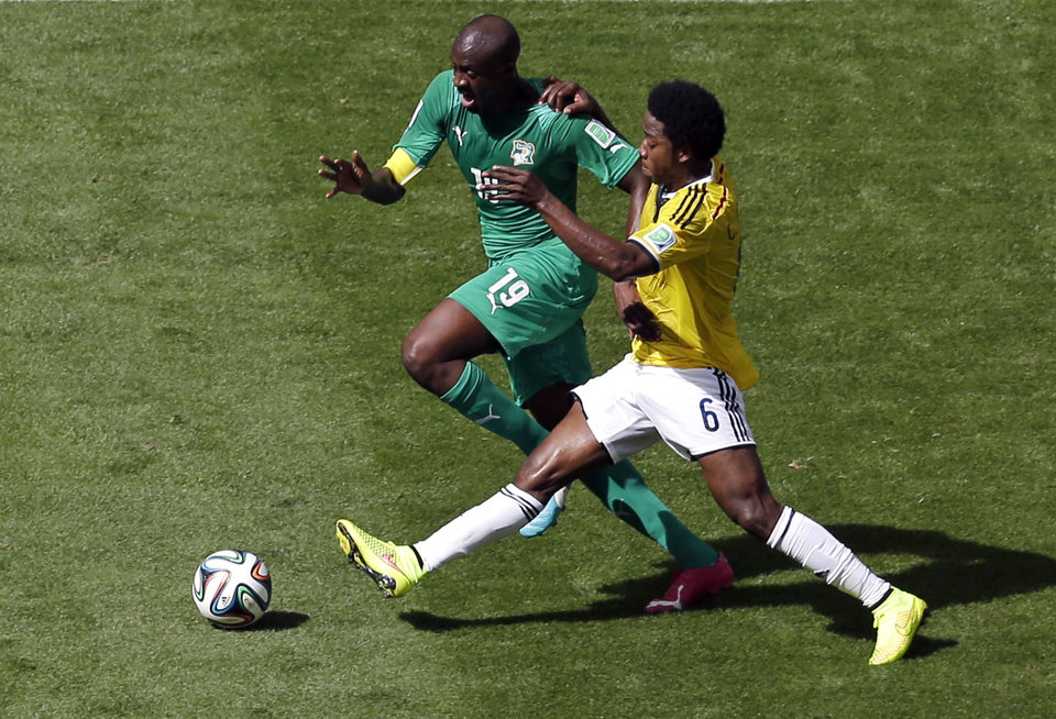 Photo - Ivory Coast's Yaya Toure controls the ball past Colombia's Carlos Sanchez Moreno during the group C World Cup soccer match between Colombia and Ivory Coast at the Estadio Nacional in Brasilia, Brazil, Thursday, June 19, 2014.  (AP Photo/Themba Hadebe)