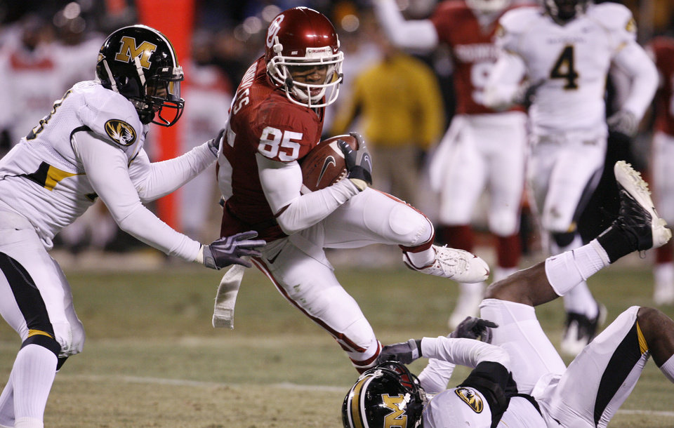 Photo - Oklahoma's Ryan Broyles (85) takes the ball up field through Missouri's Carl Gettis (19) and Justin Garrett (8) during the first half of the Big 12 Championship college football game between the University of Oklahoma Sooners (OU) and the University of Missouri Tigers (MU) on Saturday, Dec. 6, 2008, at Arrowhead Stadium in Kansas City, Mo. 