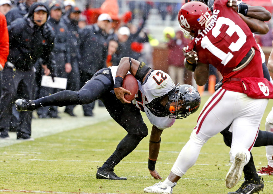 Photo - Oklahoma State's Justice Hill (27) stries to keep his balance on a carry during the Bedlam college football game between the Oklahoma Sooners (OU) and the Oklahoma State Cowboys (OSU) at Gaylord Family - Oklahoma Memorial Stadium in Norman, Okla., Saturday, Dec. 3, 2016. Photo by Steve Sisney, The Oklahoman