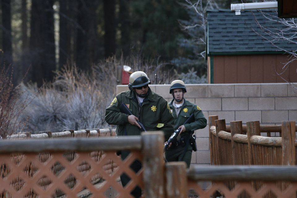 Photo - San Bernardino County sheriff's deputies search a home during a manhunt for former Los Angeles officer Christopher Dorner in Big Bear, Calif, Thursday, Feb. 7, 2013. The ex-Los Angeles police officer who authorities say went on a killing spree to punish those he blamed for his firing killed three people, set off a manhunt that stretched across three states and into Mexico, and stirred fear throughout the region. (AP Photo/Jae C. Hong)