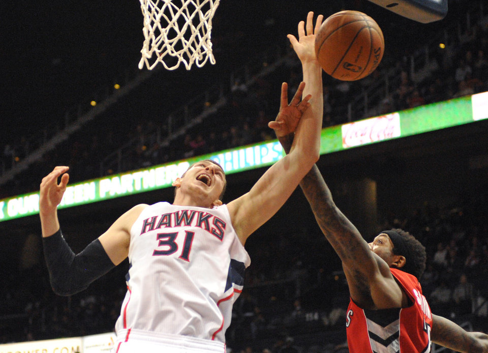 Photo - Toronto Raptors' John Salmons, right, makes contact with Atlanta Hawks' Mike Muscala (31) in the first half of their NBA basketball game Tuesday, March 18, 2014, in Atlanta. (AP Photo/David Tulis)