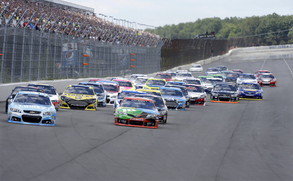 Photo - Driver Jimmie Johnson (48), left,  is pursued by Kyle Busch (18), front right, as he leads early in an NASCAR Sprint Cup Series auto race, Sunday Aug. 4, 2013, at Pocono Raceway in Long Pond, Pa. (AP Photo/Mel Evans)