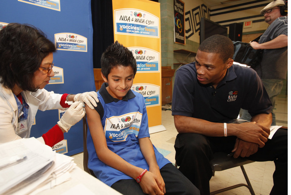 Photo - Oklahoma City Thunder NBA basketball player Russell Westbrook at Roosevelt Middle School on Thursday, Dec. 16, 2010, to promote teenage immunizations. Juan Trujillo and Westbrook.  Giving the injection is Maria Martinez with Maxim. Photo by Jim Beckel, The Oklahoman ORG XMIT: KOD