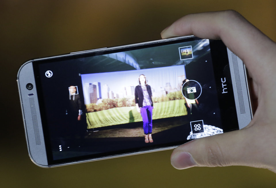Photo -  The new HTC One M8 is demonstrated,  March 25 in New York. HTC is updating its flagship HTC One smartphone by giving it a larger screen, better software and a camera that's easier to use. AP File Photo   Mark Lennihan -  AP