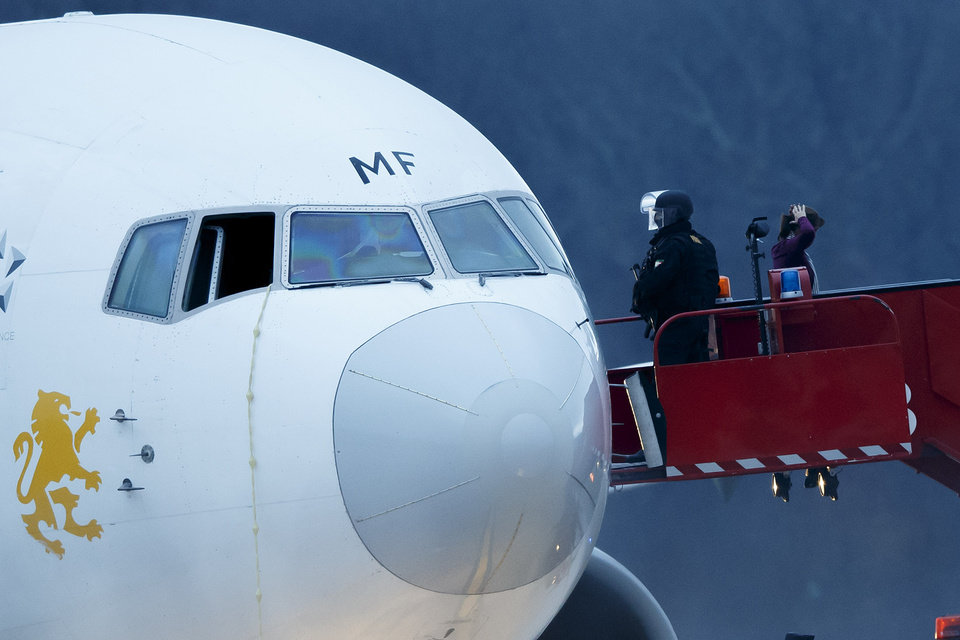 Photo - Police stand on the stairs after passengers were evacuated from a hijacked Ethiopian Airlines Plane on the airport in Geneva, Switzerland, Monday, Feb. 17, 2014.The  aircraft traveling from Addis Abeda, Ethiopia, to Rome, Italy, has landed at Geneva's international airport early Monday morning. Swiss authorities have arrested the co-pilot.  (AP Photo/Keystone, Salvatore Di Nolfi)