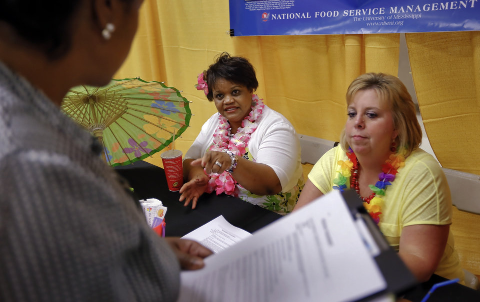 Photo -  Oklahoma City Public Schools child nutrition services employees Brinda Embery, left, and Karen Davis talk to an applicant during the job fair Tuesday.   CHRIS LANDSBERGER -  CHRIS LANDSBERGER