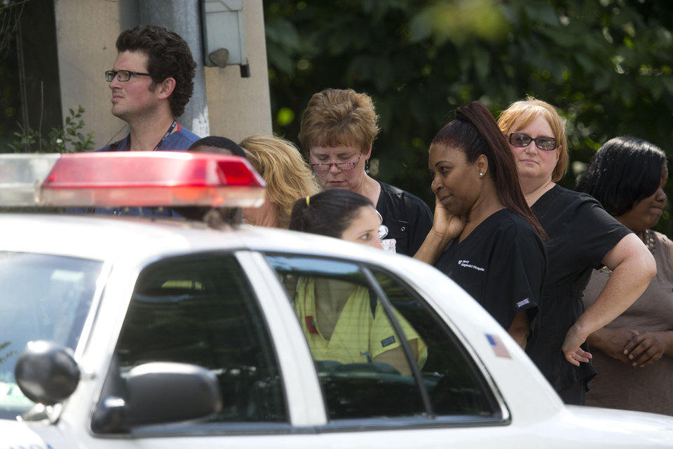 Photo - Hospital workers view police activity at the scene of a shooting Thursday, July 24, 2014,  at Mercy Fitzgerald Hospital in Darby, Pa. Police in suburban Philadelphia are investigating a shooting at the hospital campus and say they have reports people have been injured and a suspect is in custody. (AP Photo)