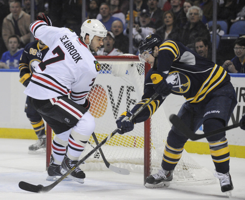 Photo - Buffalo Sabres' Drew Stafford, right, backhands the puck for a first-period goal as Chicago Black Hawks' Brent Seabrook arrives too late during the first period of an NHL hockey game in Buffalo, N.Y., Sunday, March 9,  2014. (AP Photo/Gary Wiepert)