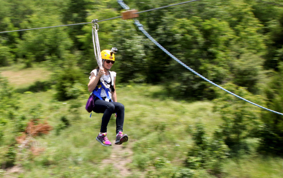 Molly Bullock comes into a platform during a Zipline Canopy Tour at Postoak Lodge and Retreat in north Tulsa. JOHN CLANTON/Tulsa World <strong>John Clanton</strong>
