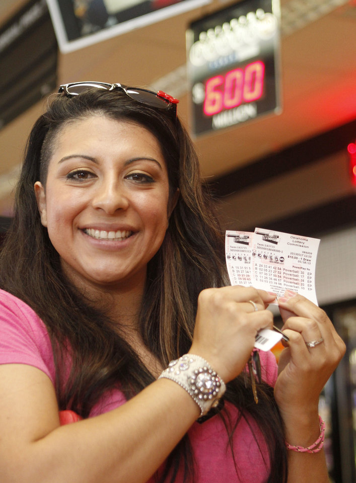 Photo - Giovannia Gonzalez shows the lottery tickets she purchased at the OnCue store at N 23 and Santa Fe Avenue in Oklahoma City. Photo By Paul Hellstern, The Oklahoman  PAUL HELLSTERN - Oklahoman